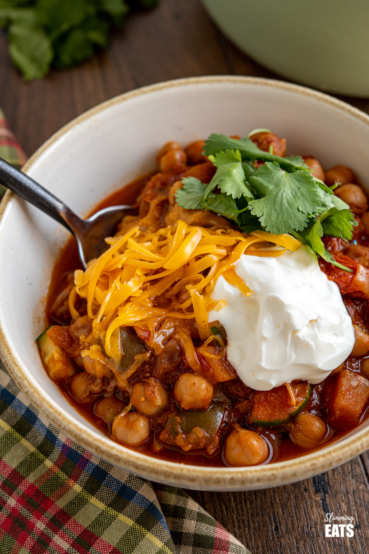 close up of chickpea vegetable chilli in bowl with cheddar, sour cream and cilantro