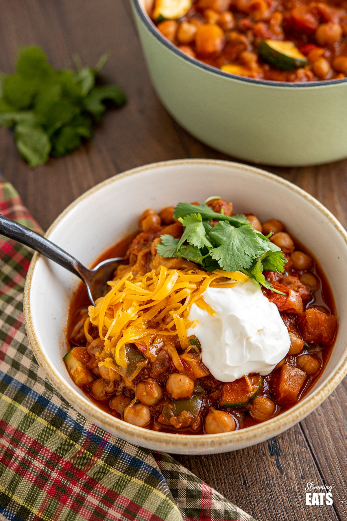 chickpea vegetable chilli in a bowl topped with cheddar, sour cream and cilantro
