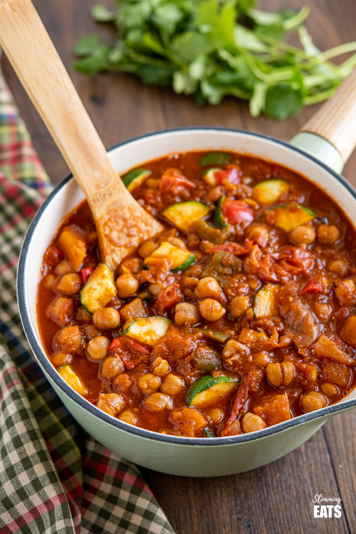 chickpea vegetable chilli in a wooden handled cast iron pan with wooden spoon