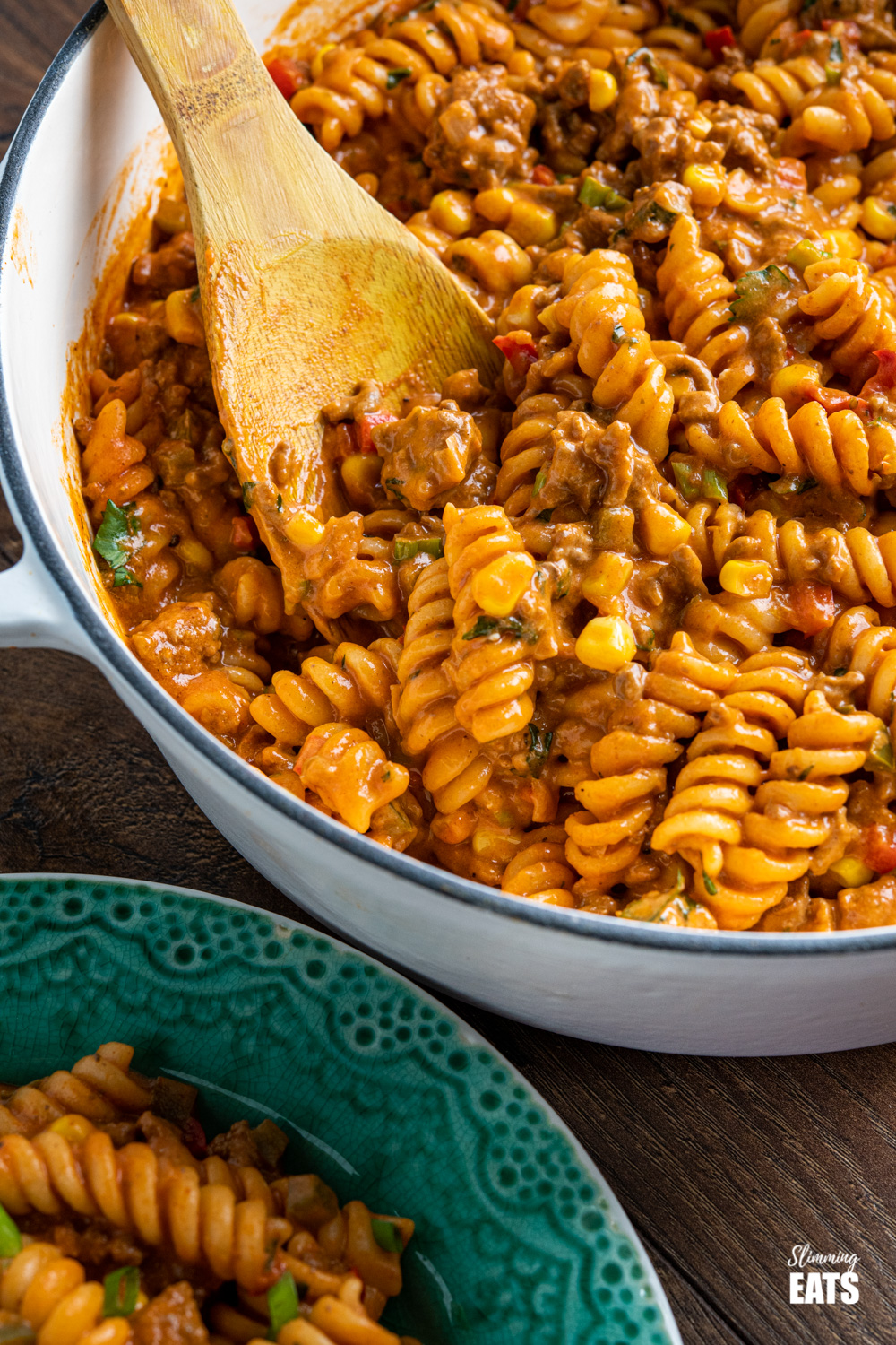 close up of One Pot Taco Beef Pasta in skillet with wooden spoon