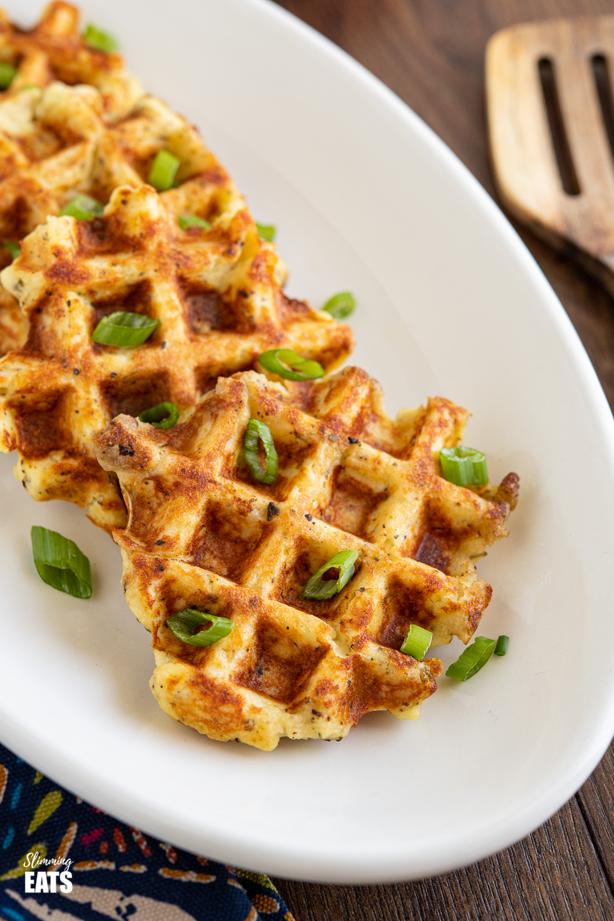 close up of Leftover Mash Potato Waffles on white oval plate