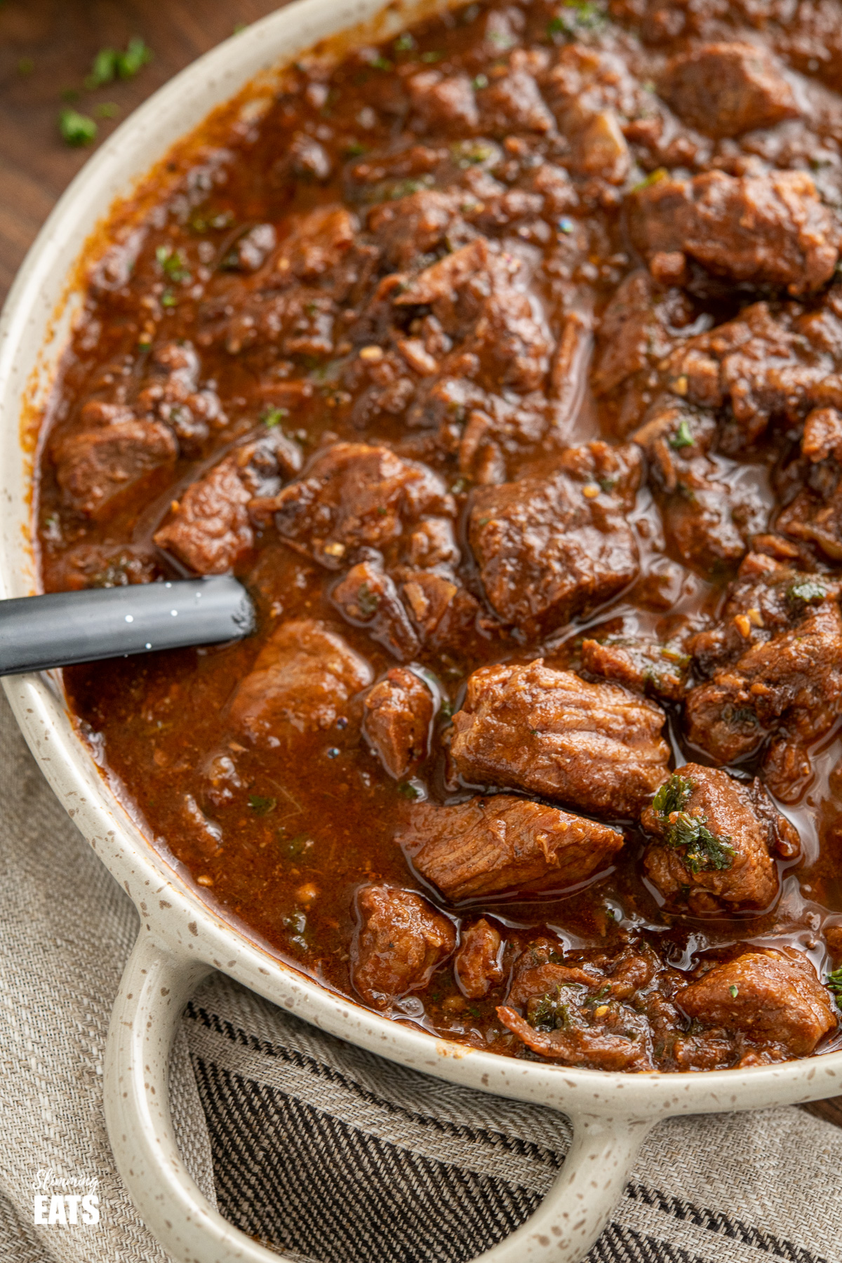 close up of Beef and prune stew in brown grey serving dish