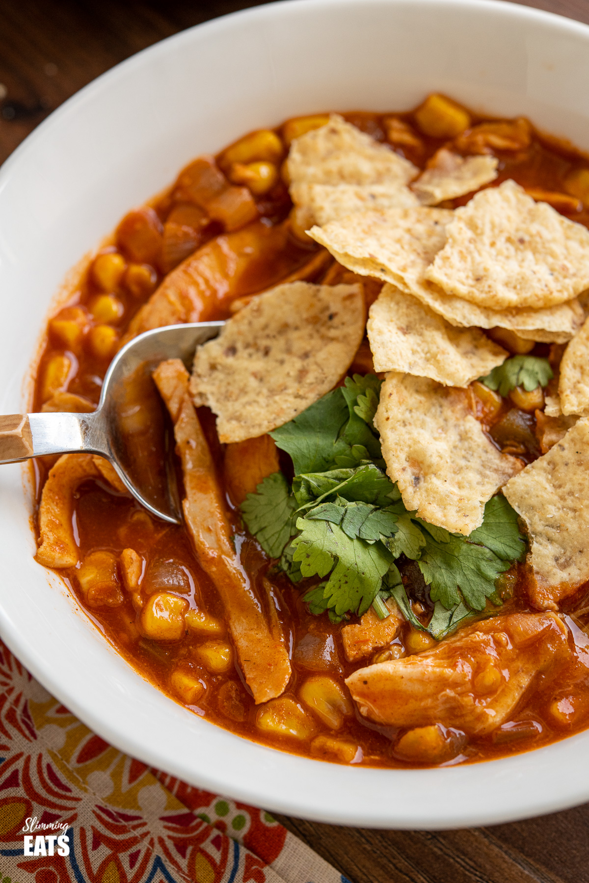 close up of white bowl of Easy Chicken Tortilla Soup with crushed tortilla chips