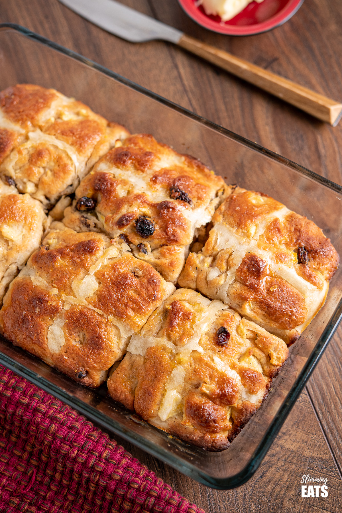 close up of hot cross buns in a glass baking dish