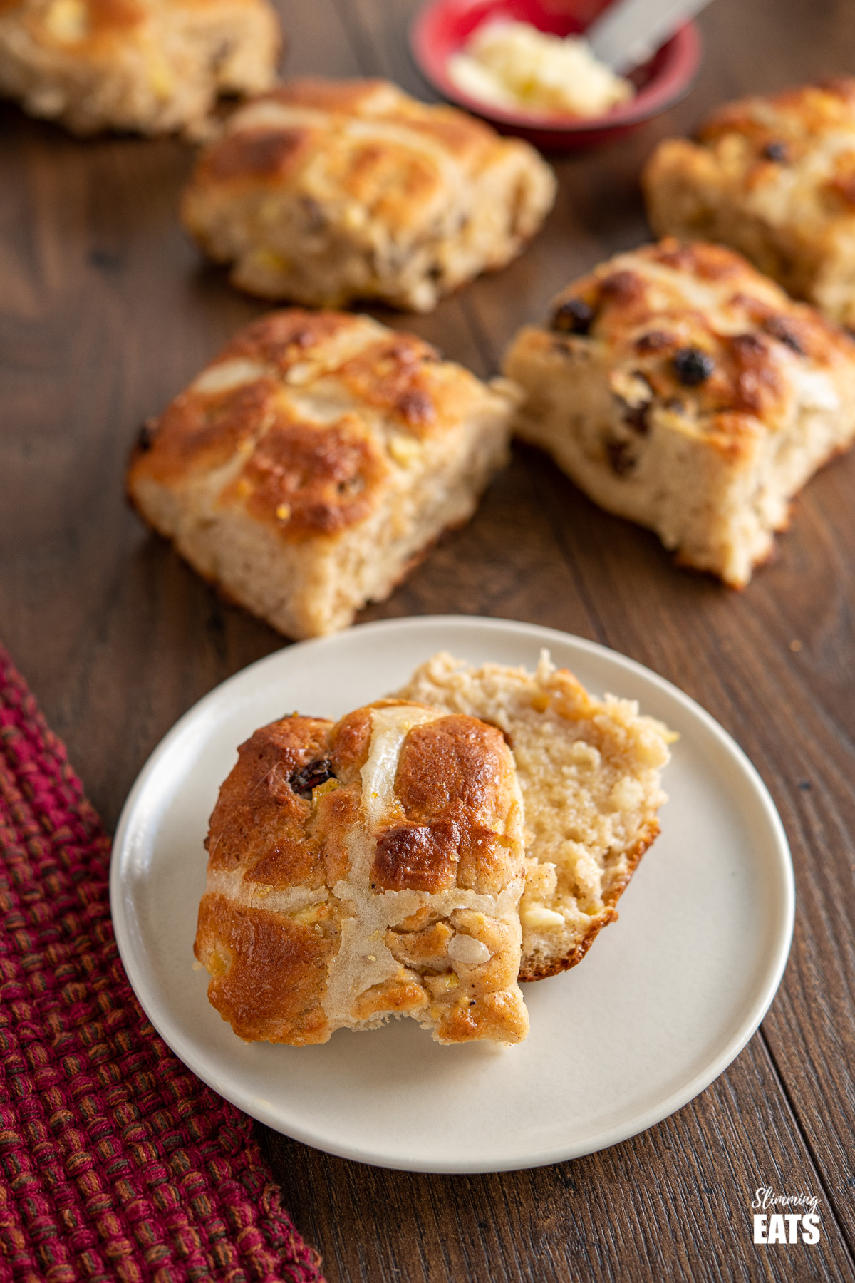 sliced hot cross bun on a plate with scattered hot cross buns in the background
