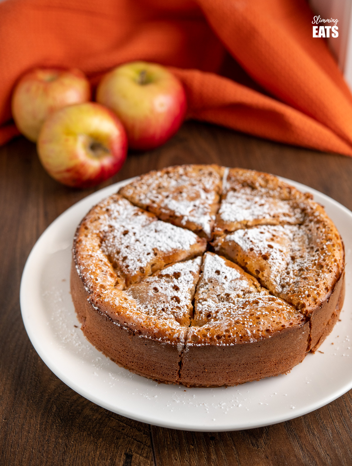 apple sultana cake on white plate with scattered apples and orange cloth in background