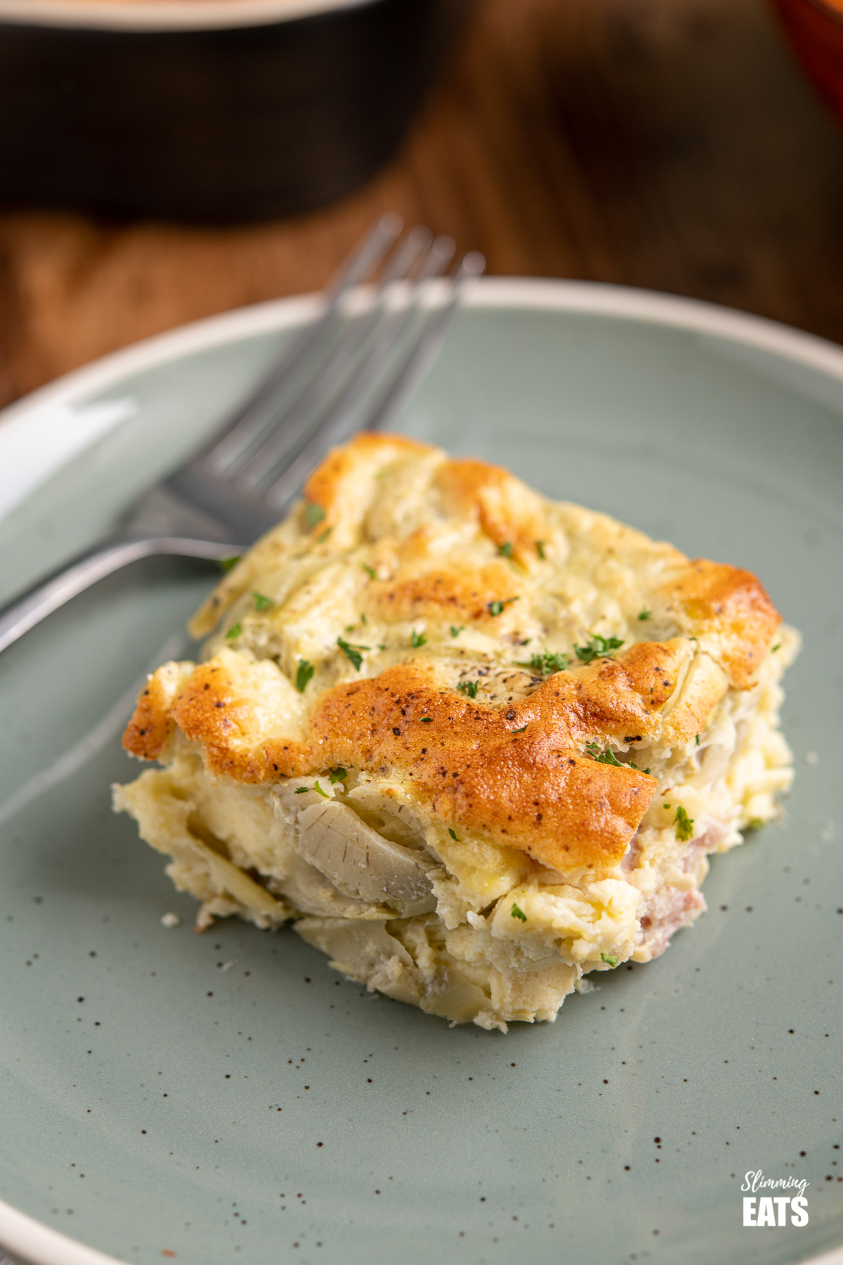 slice of Artichoke Bacon Parmesan Crustless Quiche on green blue plate with fork