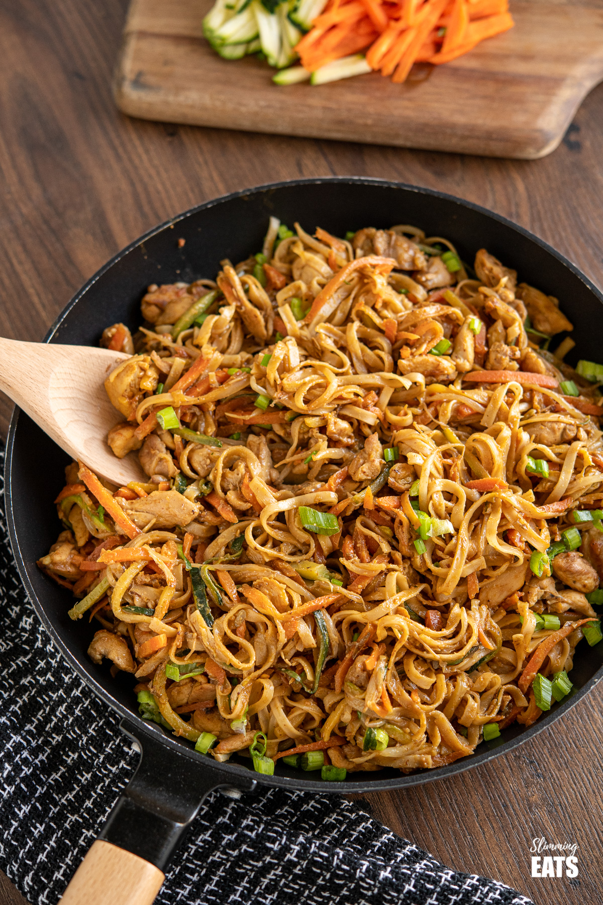 Easy Peanut Chicken Noodles in frying pan with wooden spoon, chopping board with carrots and zucchini in background