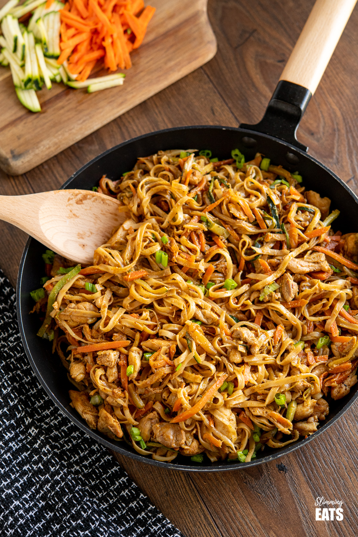 Easy Peanut Chicken Noodles in black frying pan with wooden handle, chopped board with carrots and zucchini in background