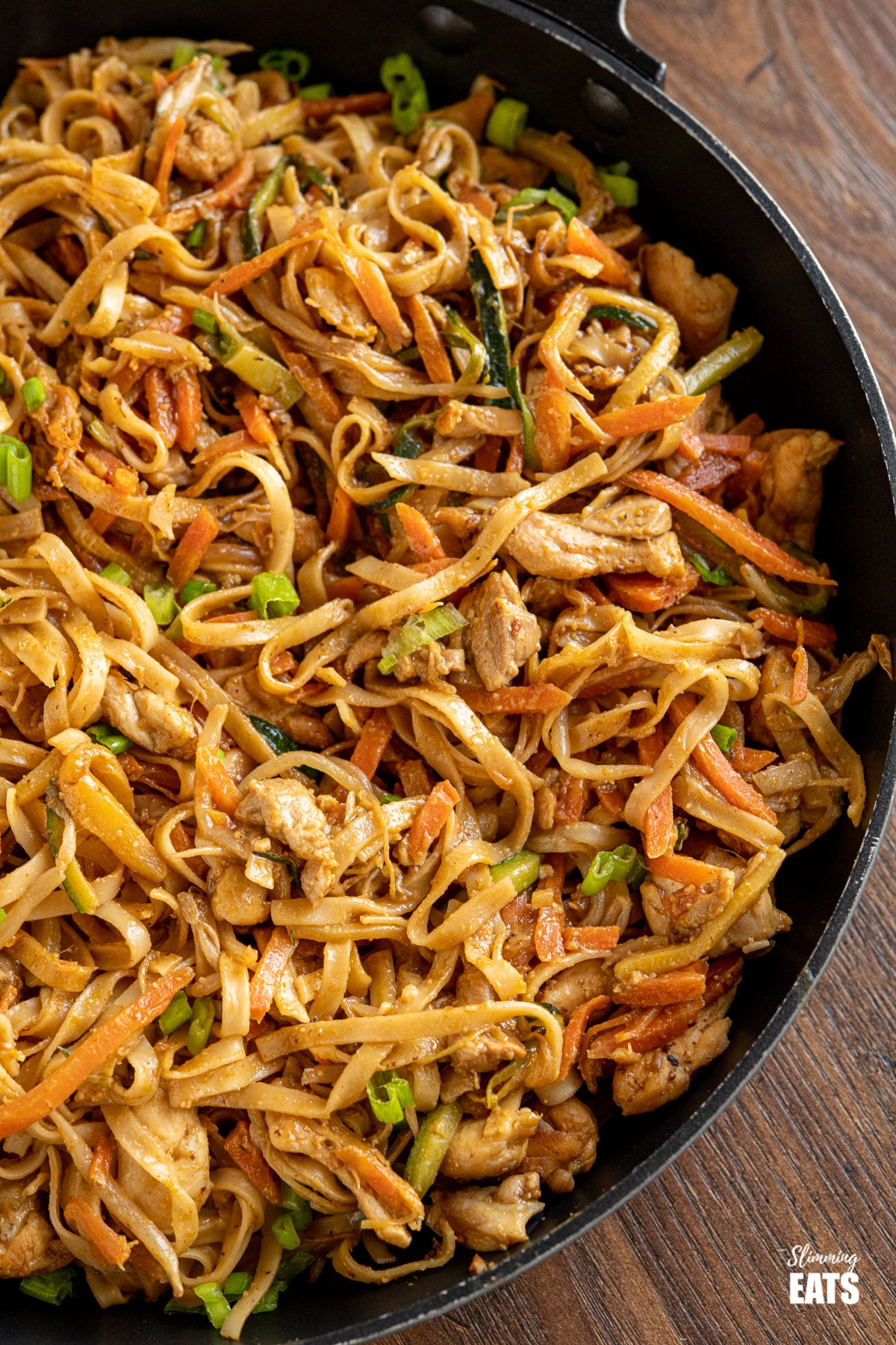 close up of Easy Peanut Chicken Noodles in black frying pan