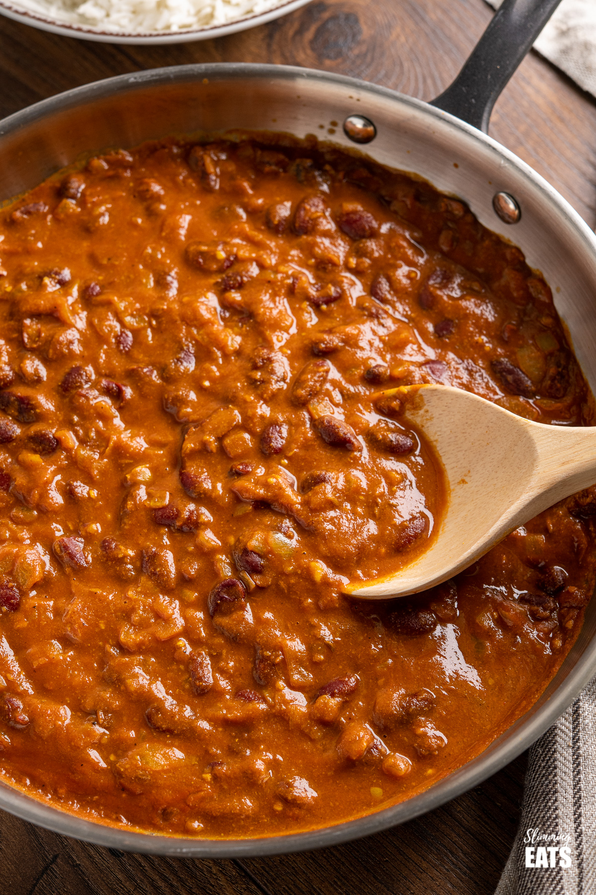close up of Kidney Bean Curry (Rajma) in stainless steel frying pan with wooden spoon