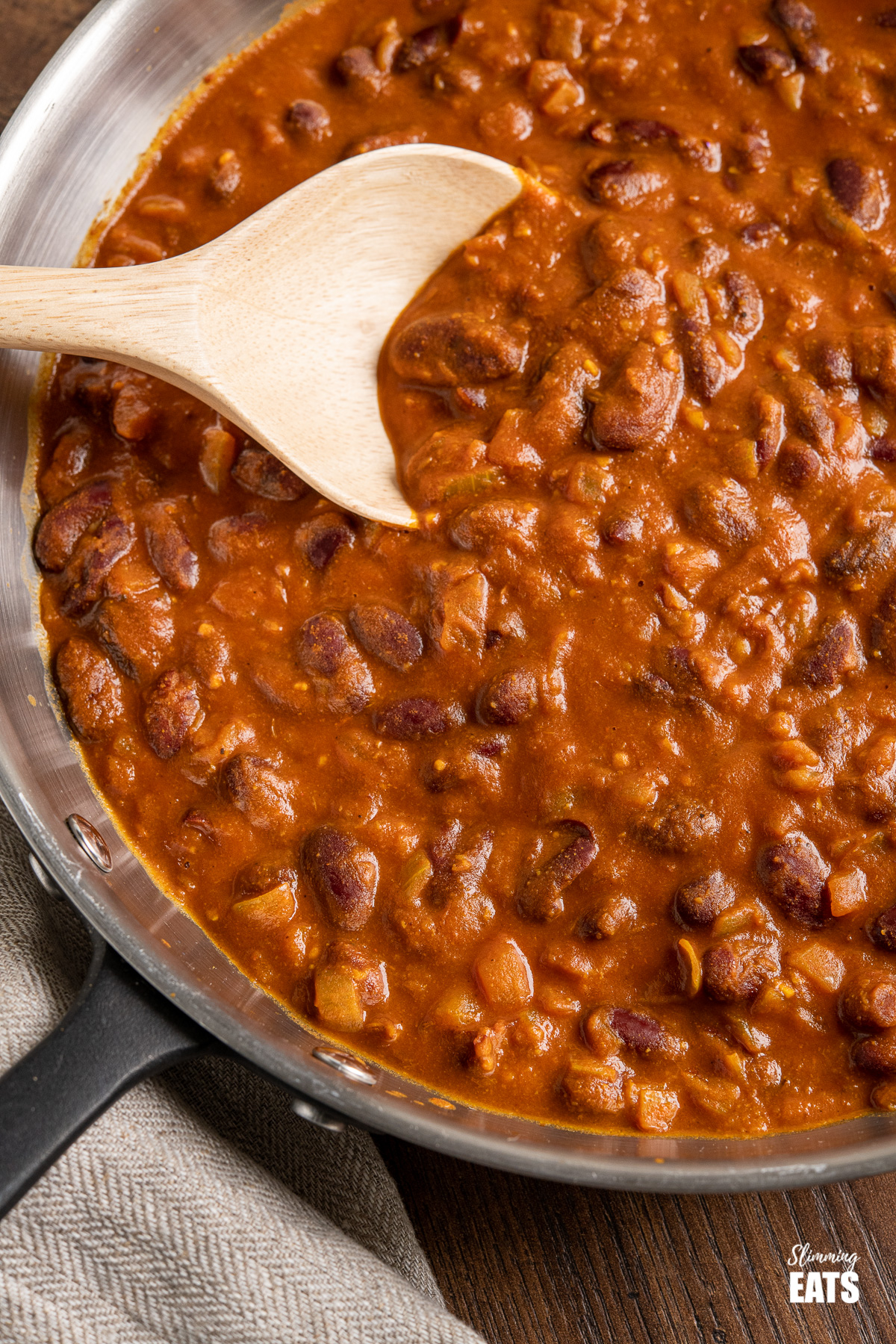 close up of Kidney Bean Curry (Rajma) in frying pan with wooden spoon