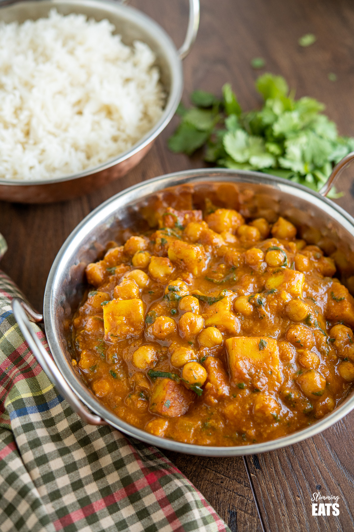 Chana Paneer in dish with rice and cilantro in the background