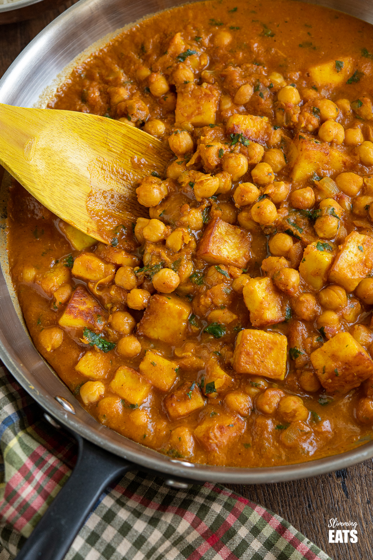 close up of Chana Paneer in black handled frying pan with wooden spoon