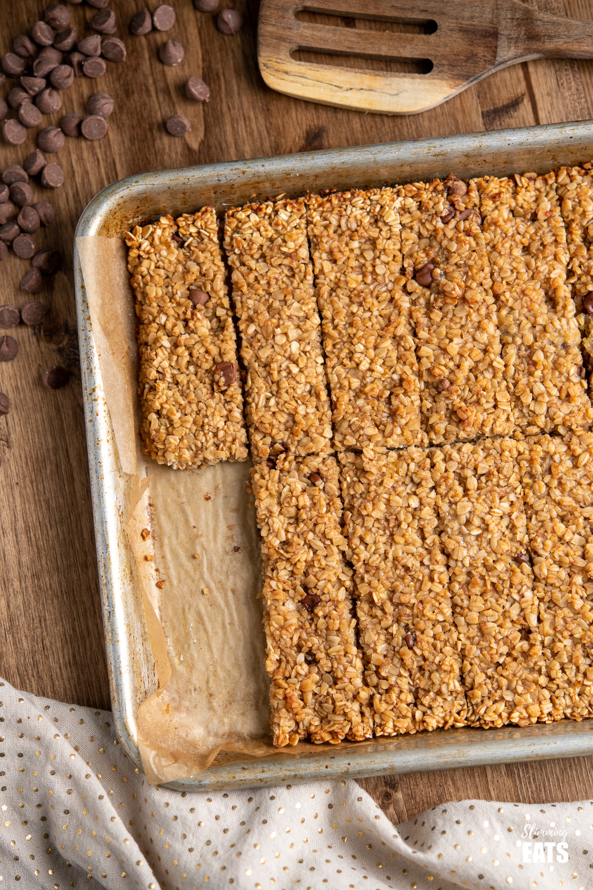 close up of Healthy Chocolate Chip Banana Granola Bars on a baking tray  with scattered chocolate chips and wooden spatula above