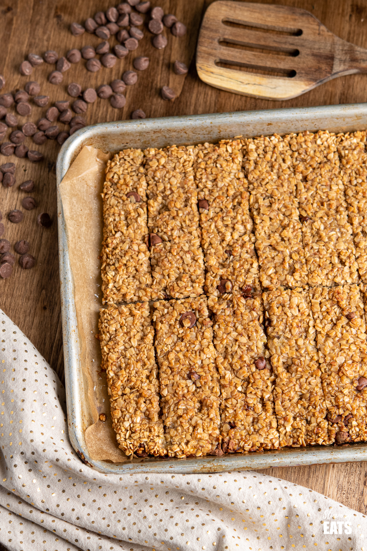 Healthy Chocolate Chip Banana Granola Bars on a baking tray with scattered chocolate chips on wooden board