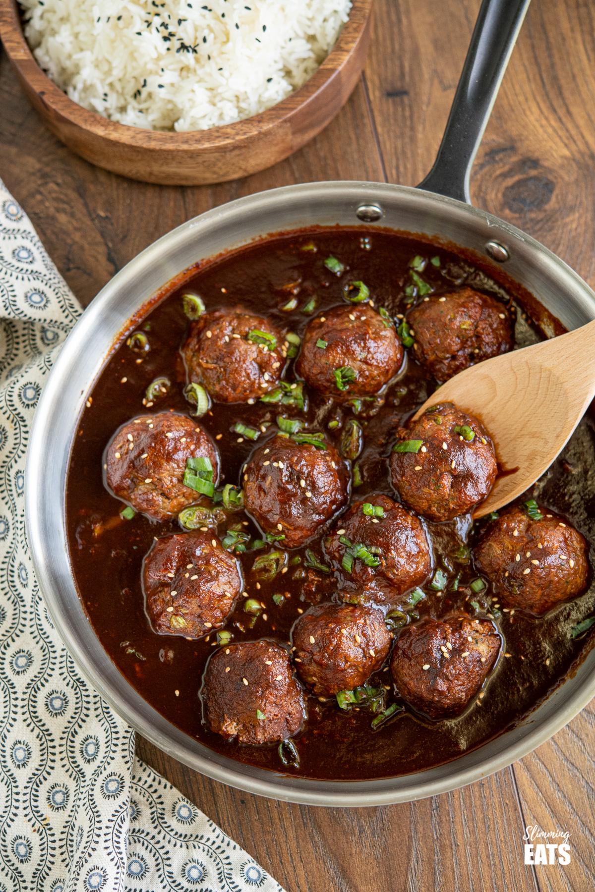 Saucy Asian Hidden Vegetable Beef Meatballs in frying pan with rice in wooden bowl