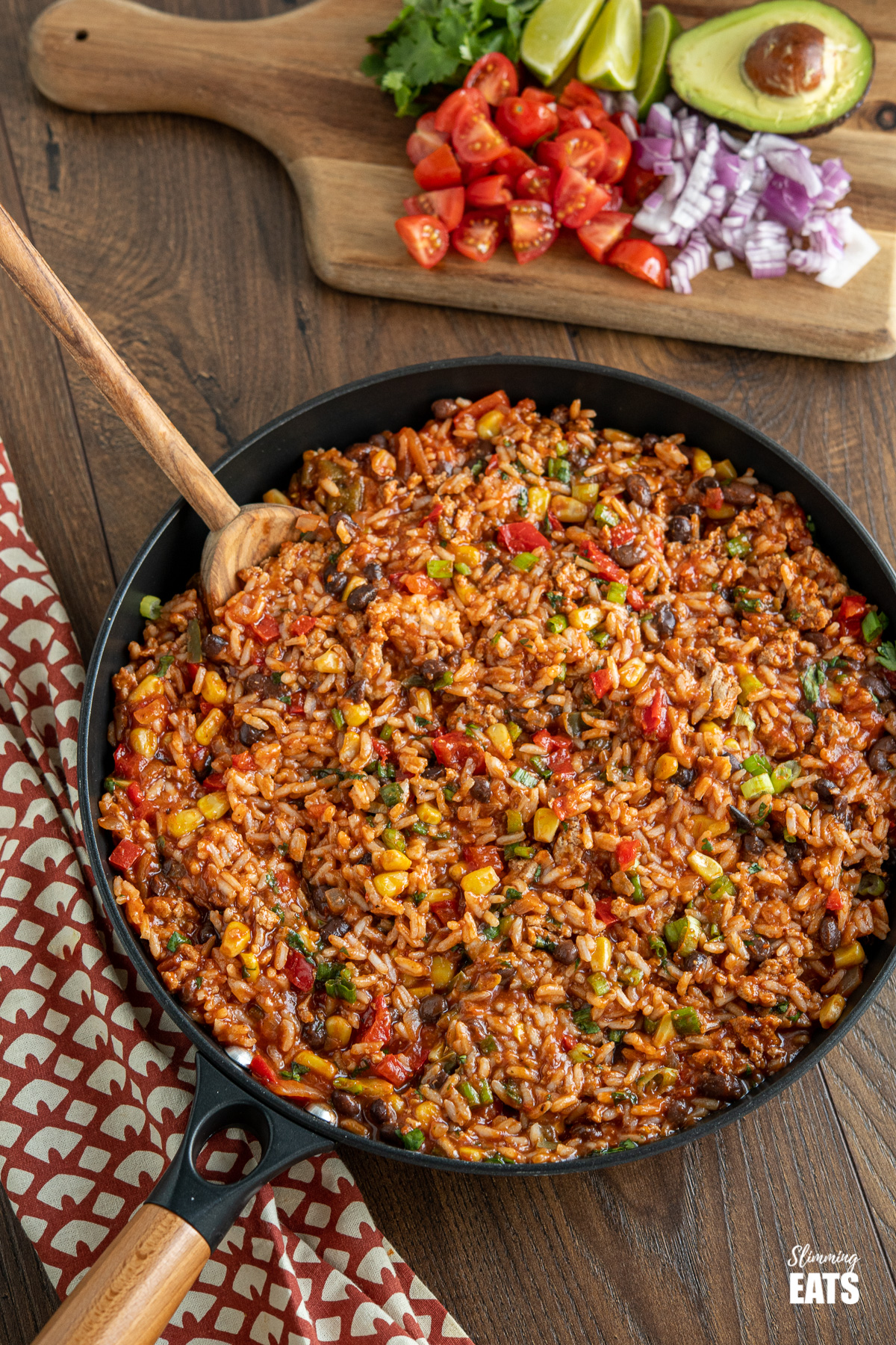 turkey burrito rice in black frying pan with wooden spoon, chopping board with toppings in background