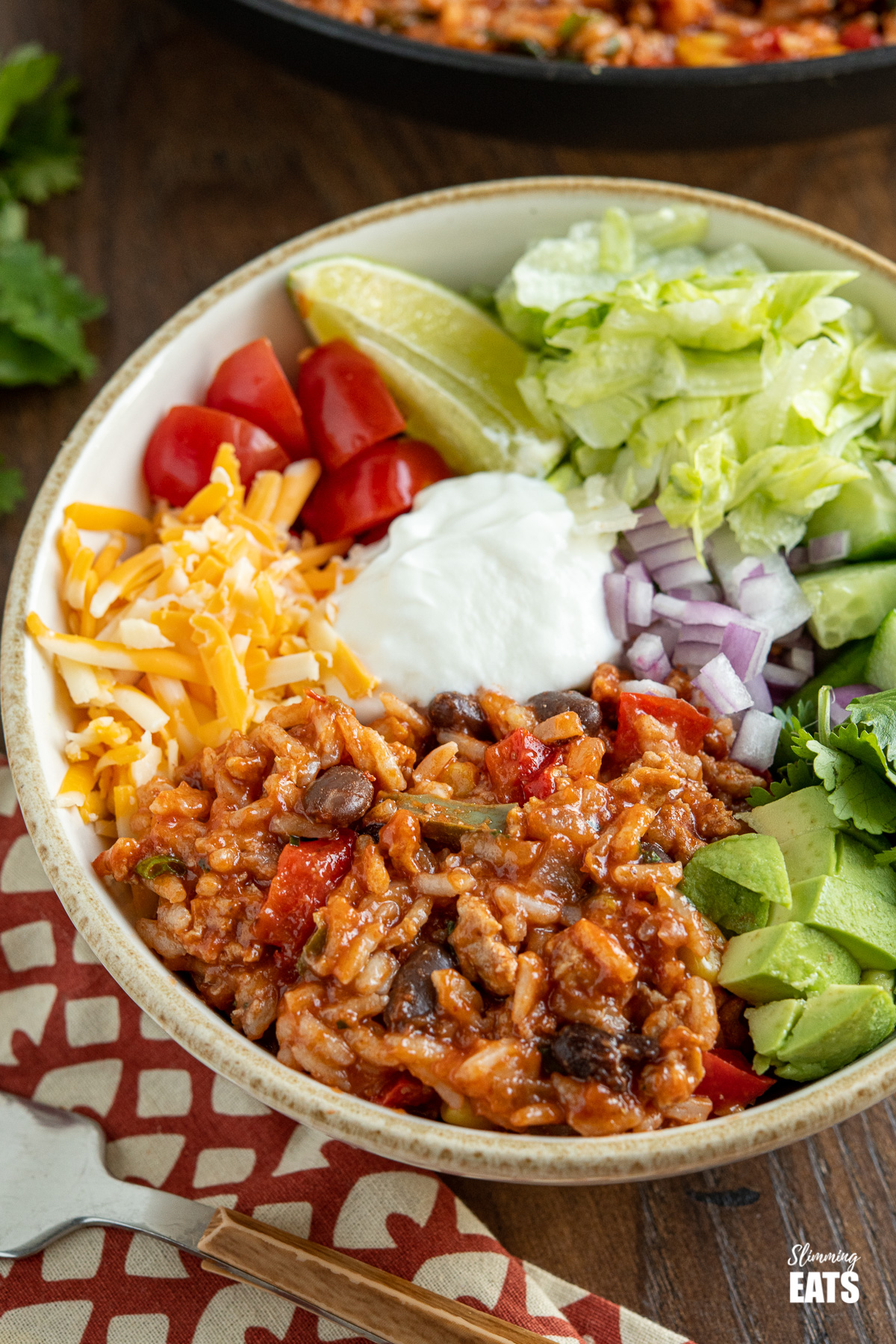 close up of turkey rice burrito bowls with toppings on wooden board