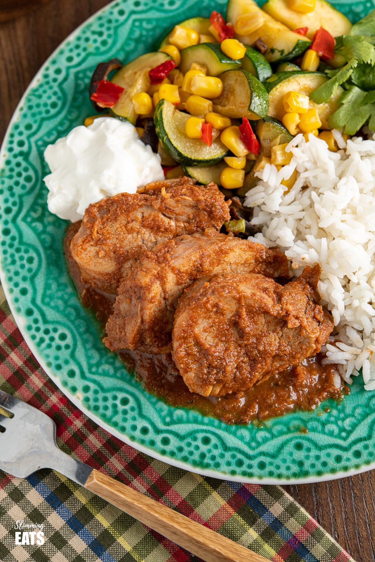 close up of sliced Slow Cooker Cajun Apple Pork Tenderloin on teal plate with sour cream, rice and vegetables
