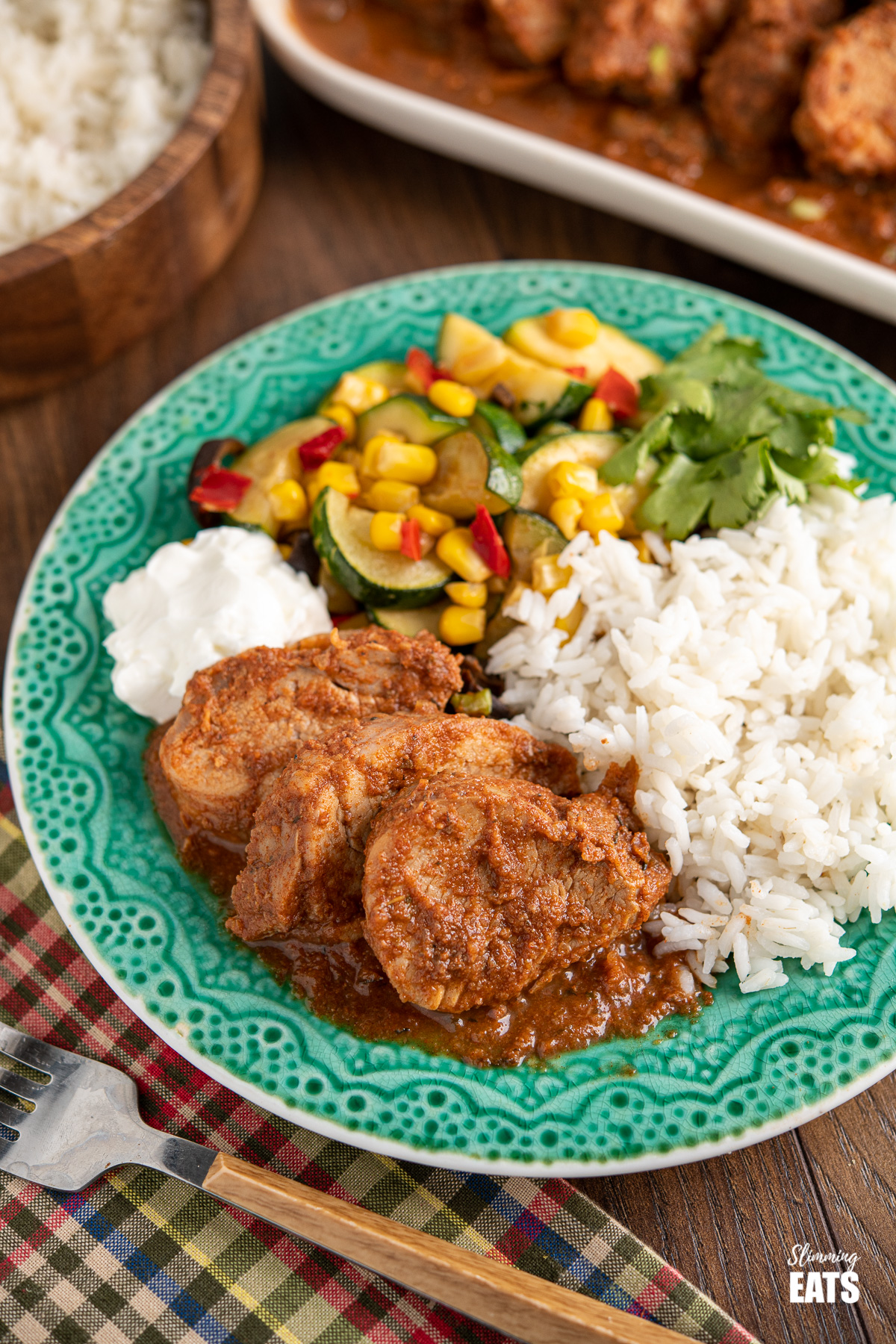 sliced Slow Cooker Cajun Apple Pork Tenderloin on teal plate with sour cream, rice and vegetables