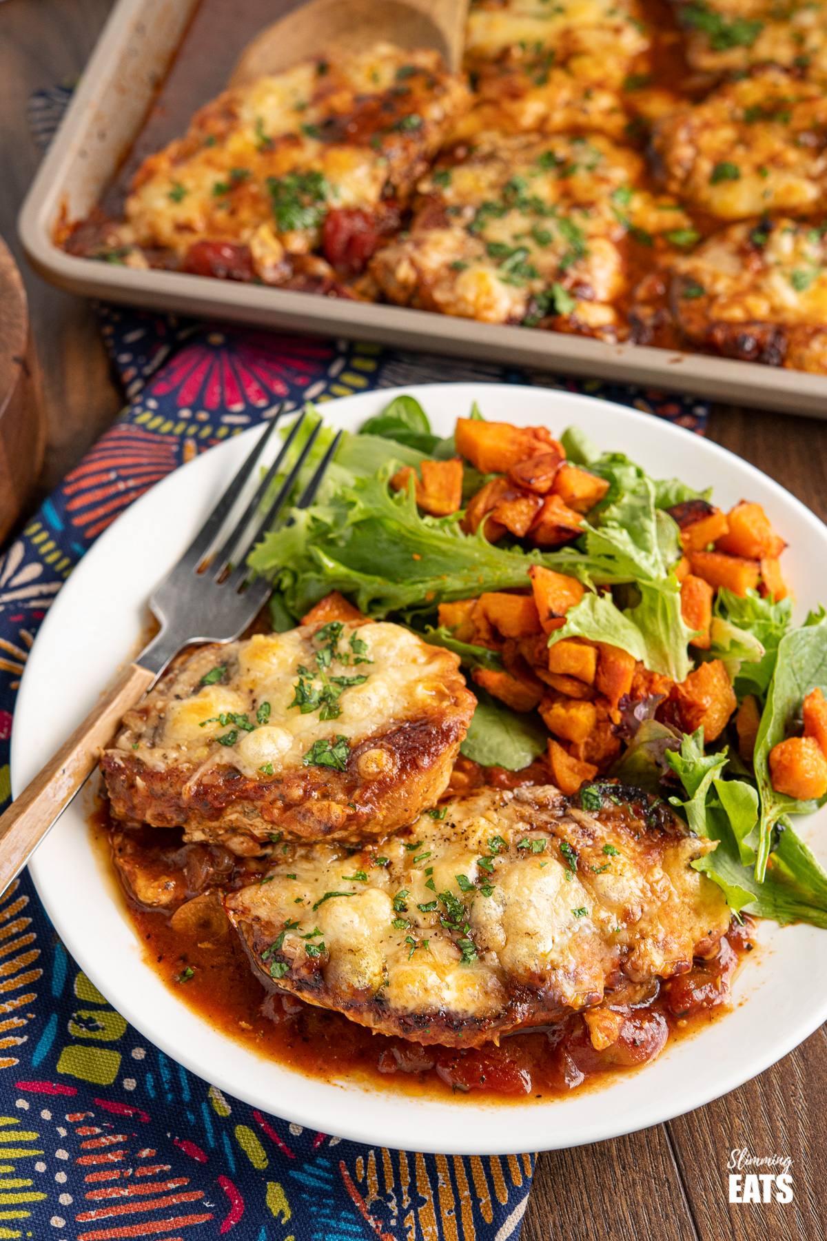 white plate of Cheesy Topped Mediterranean Pork Loin Chops and roasted butternut squash with baby green, fork to the left of plate.