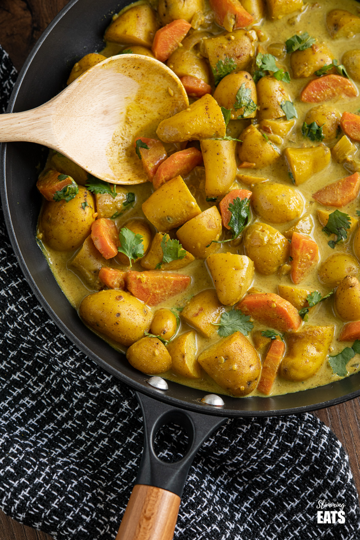 close up of creamy coconut potato curry in black frying pan with wooden handle
