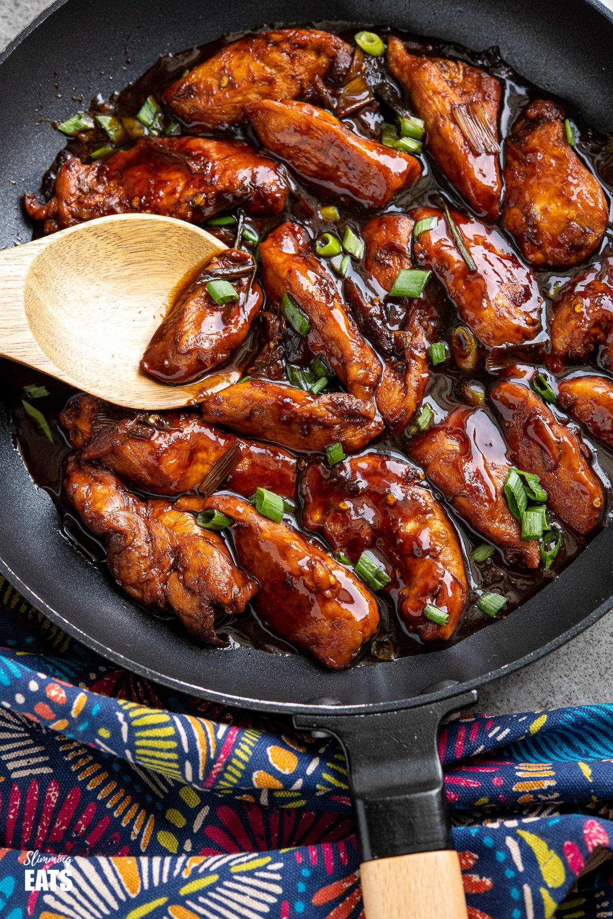 close up of Asian Sprite Chicken in black frying pan with wooden handle, wooden spoon placed in pan