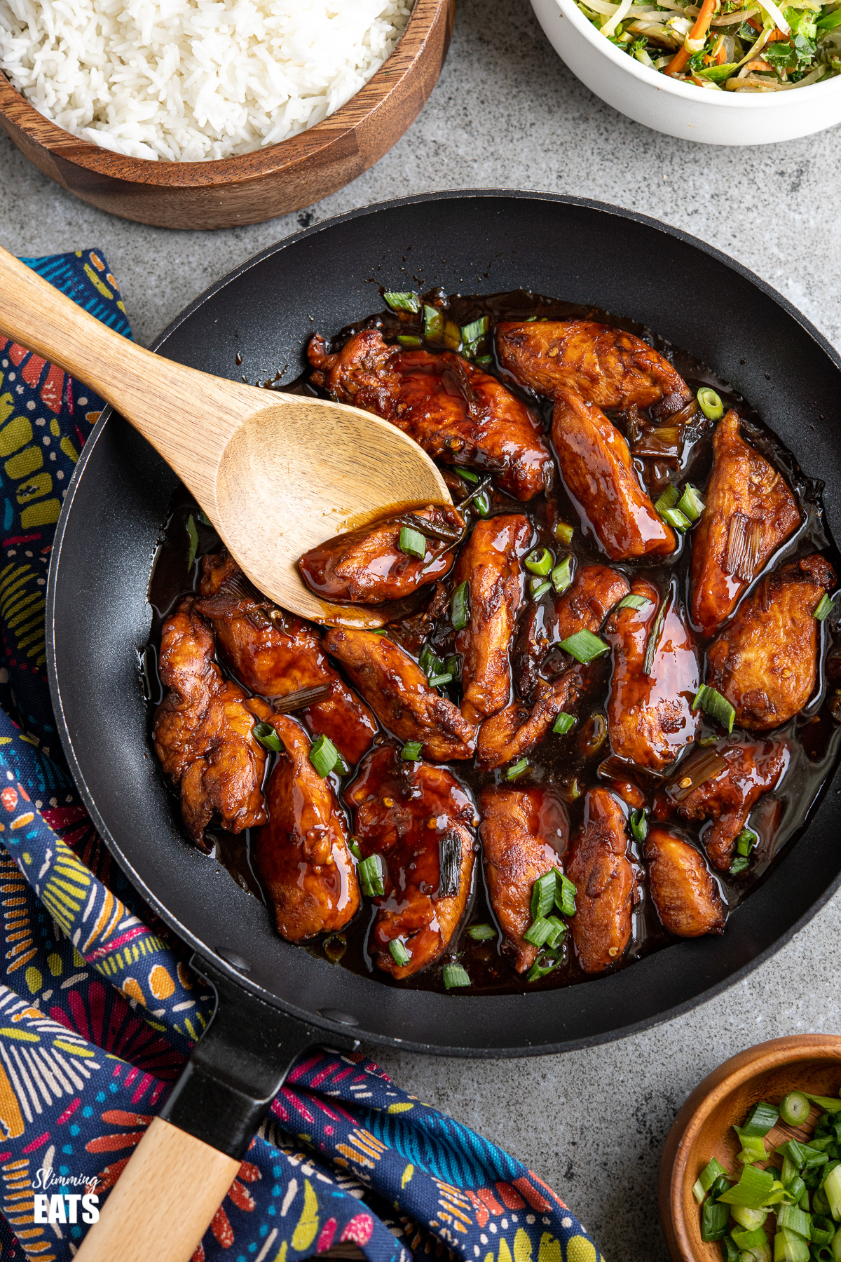 asian sprite chicken in a wooden handled black frying pan with bowl of rice and stir fried veg in background