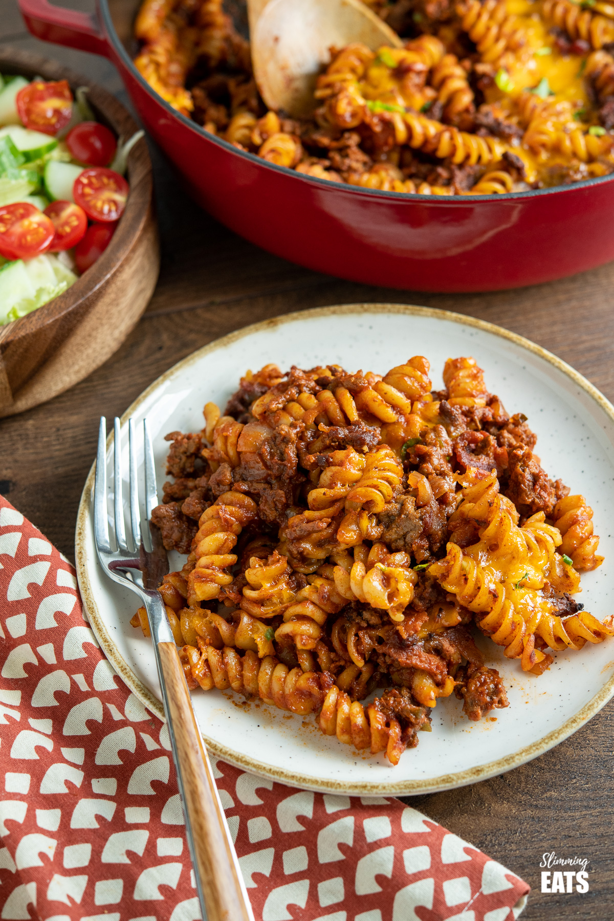 serving of BBQ Bacon Cheeseburger Pasta Bake on white plate with beige rim, fork placed to the left and a wooden bowl of salad and cast iron skillet filled with the pasta in the background