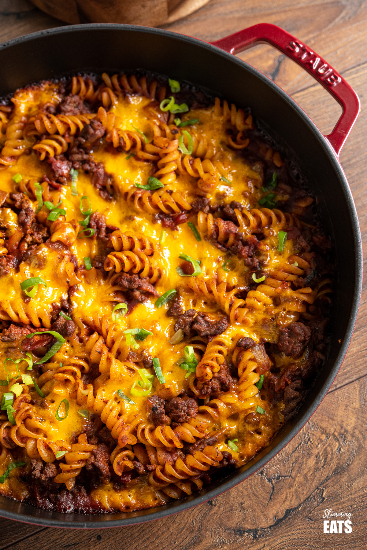 close up of BBQ Bacon Cheeseburger Pasta Bake in red cast iron skillet