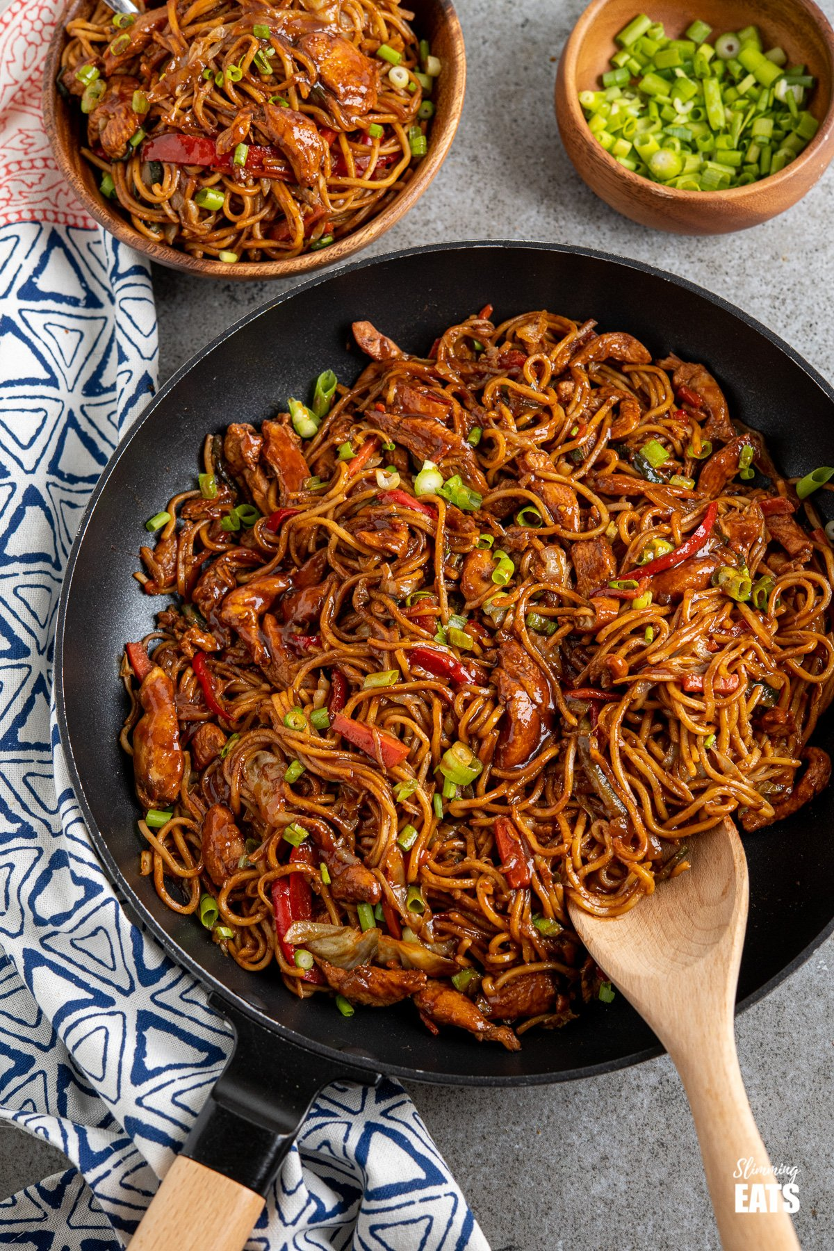 Hoisin chicken noodles in black frying pan with wooden handle, bowl of noodles and spring onions in background
