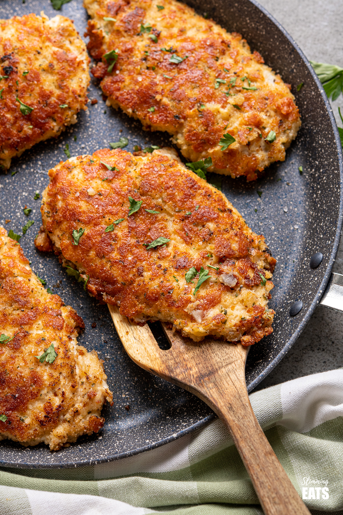 Four Golden Parmesan Crusted Chicken cutlets on frying pan with wooden spatual