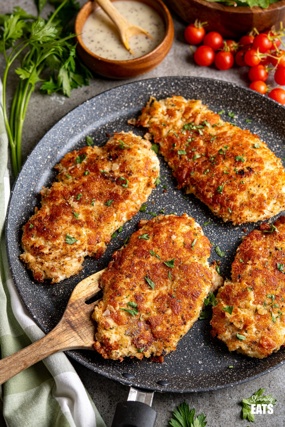 Four Golden Parmesan Crusted Chicken on frying pan with wooden spatula, tomatoes, dressing and salad in background