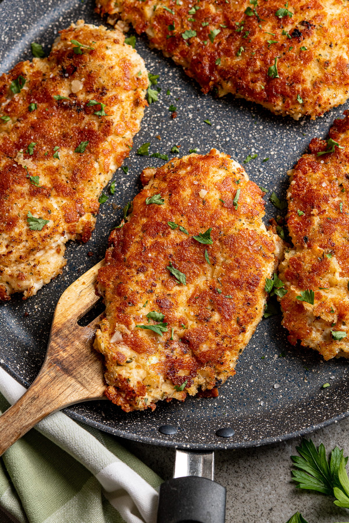 close up of Golden Parmesan Crusted Chicken cutlets on frying pan with wooden spatula