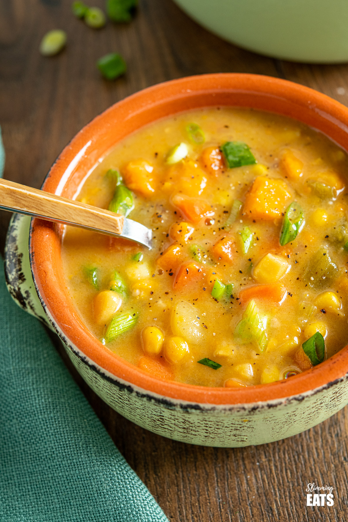 close up of bowl of vegan vegetable chowder on wooden board with spoon