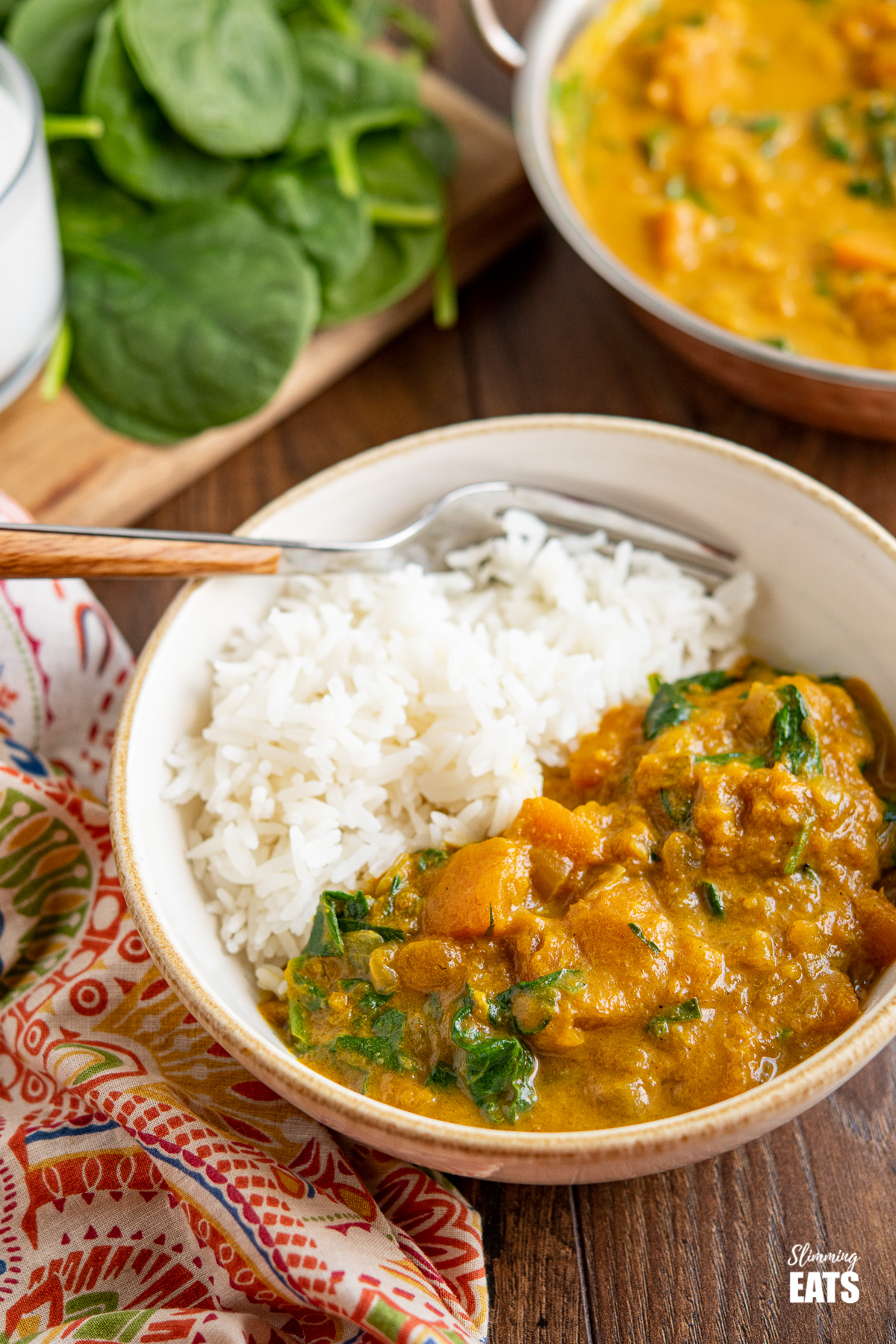 Easy Butternut Squash Curry with Spinach in a white bowl with rice, spinach and curry dish in background
