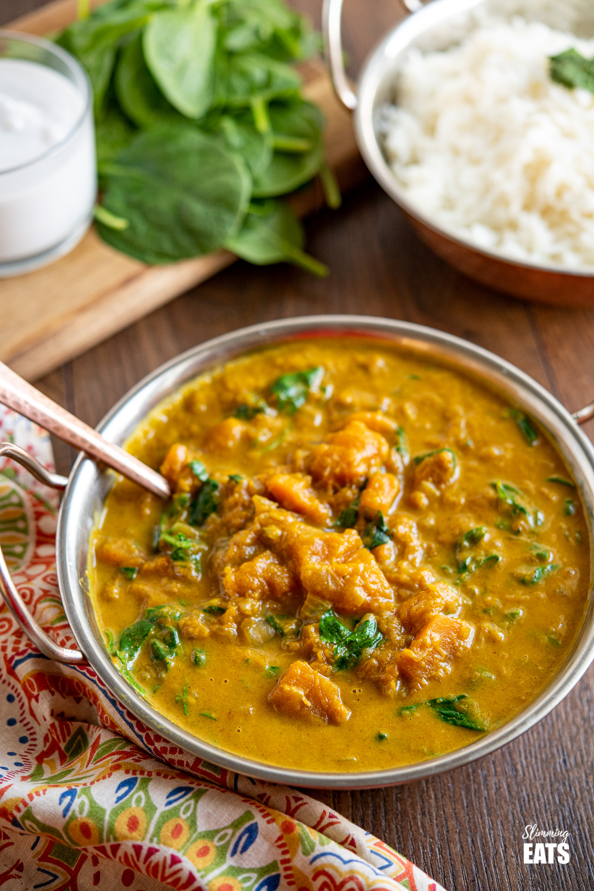 Easy Butternut Squash Curry with Spinach in metal dish with bowl of rice, spinach and coconut milk in the background