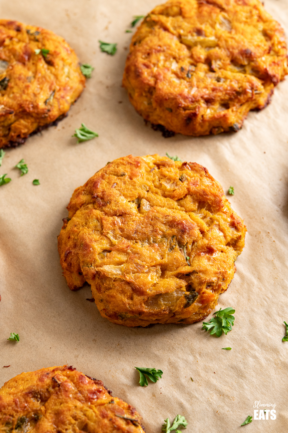 close up of tuna sweet potato patties on parchment lined baking tray