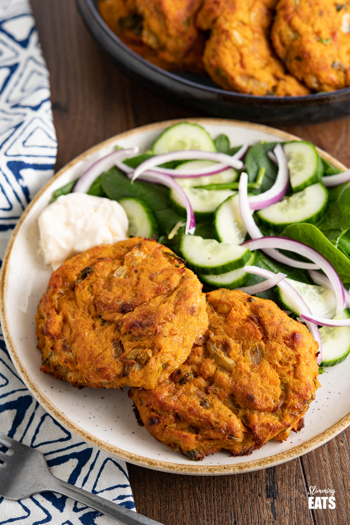 Tuna Sweet Potato Cheddar Patties on white plate with beige rim with salad and mayo