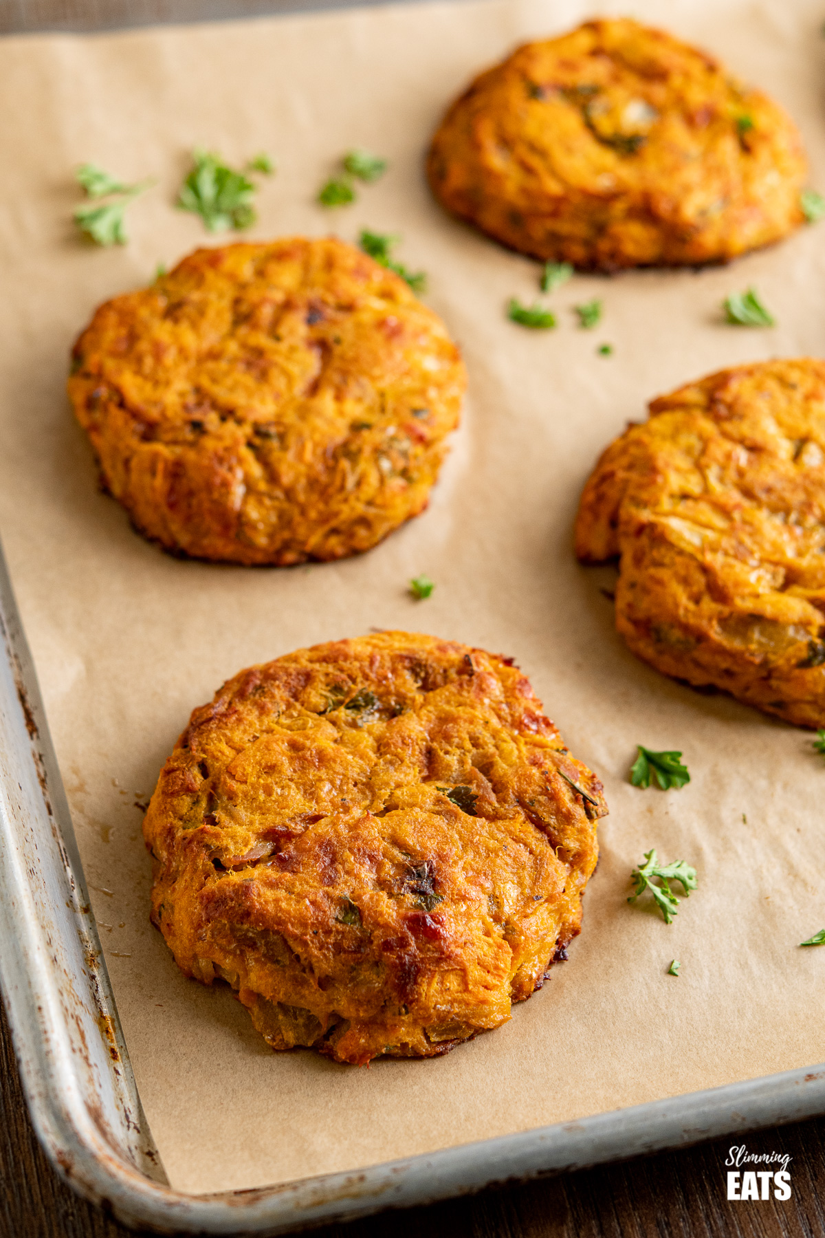 Tuna Sweet Potato Cheddar Patties on parchment lined baking tray with scattered parsley