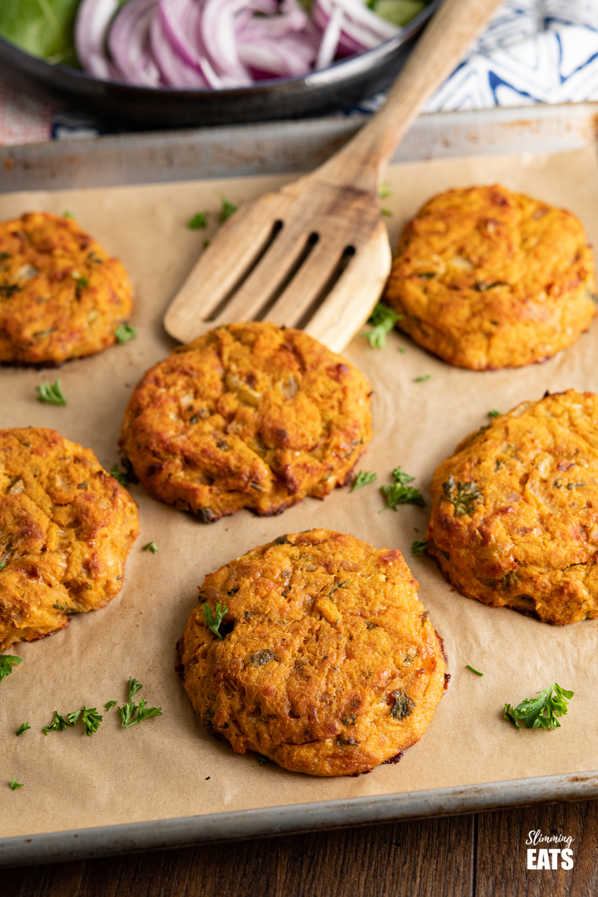 Tuna Sweet Potato Cheddar Patties on parchment lined baking tray with wooden spatula