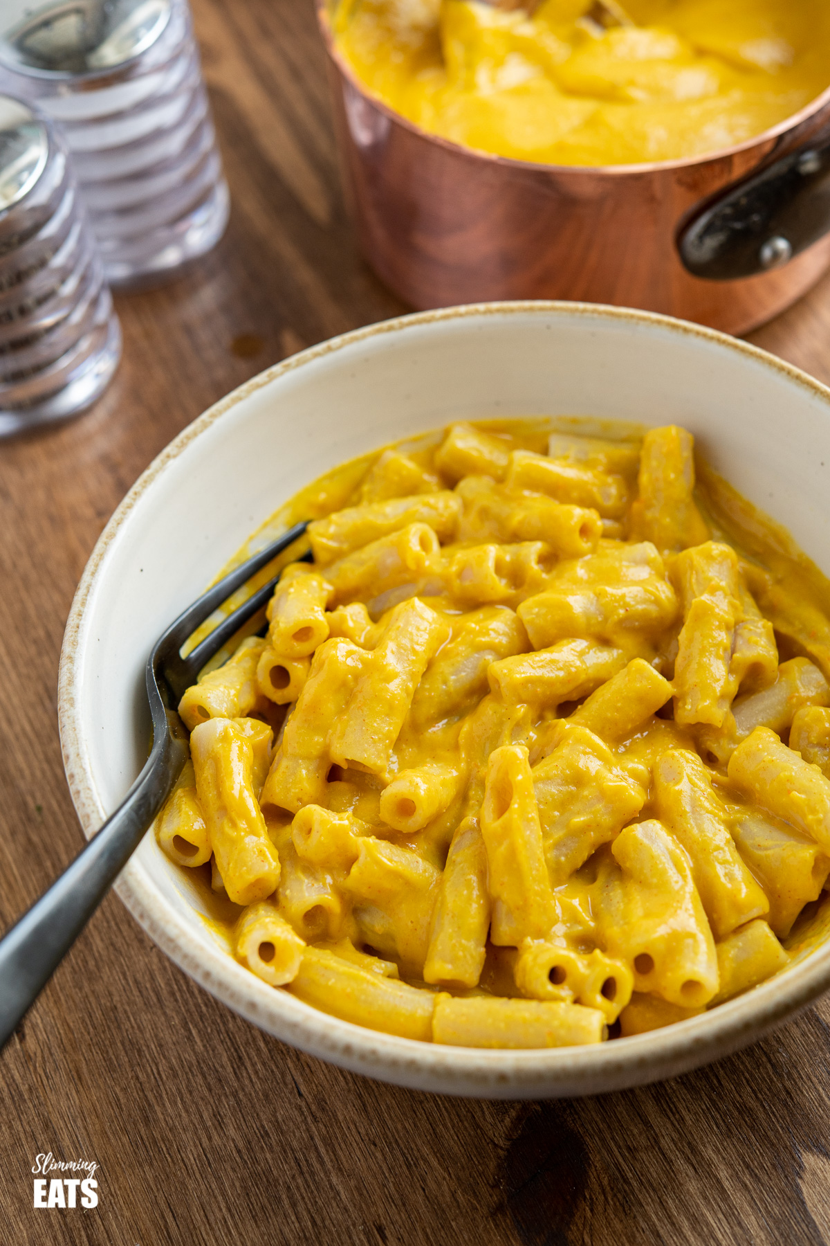 Delicious Creamy Vegan Cheese Sauce in bowl over pasta with black fork