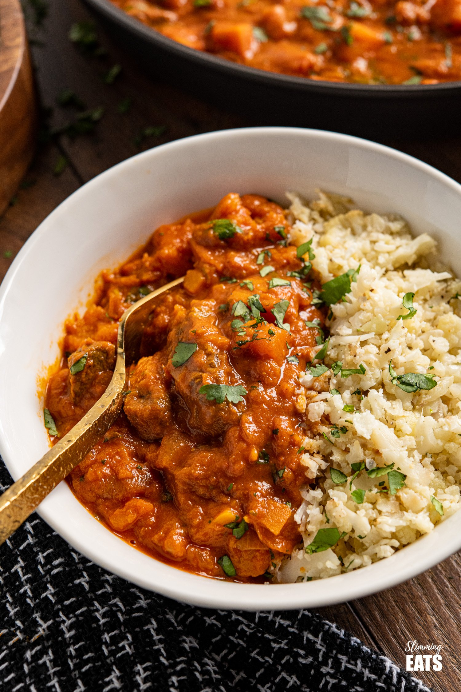 close up of Beef and Sweet Potato Tikka Masala with Cauliflower Rice in a white bowl with gold fork
