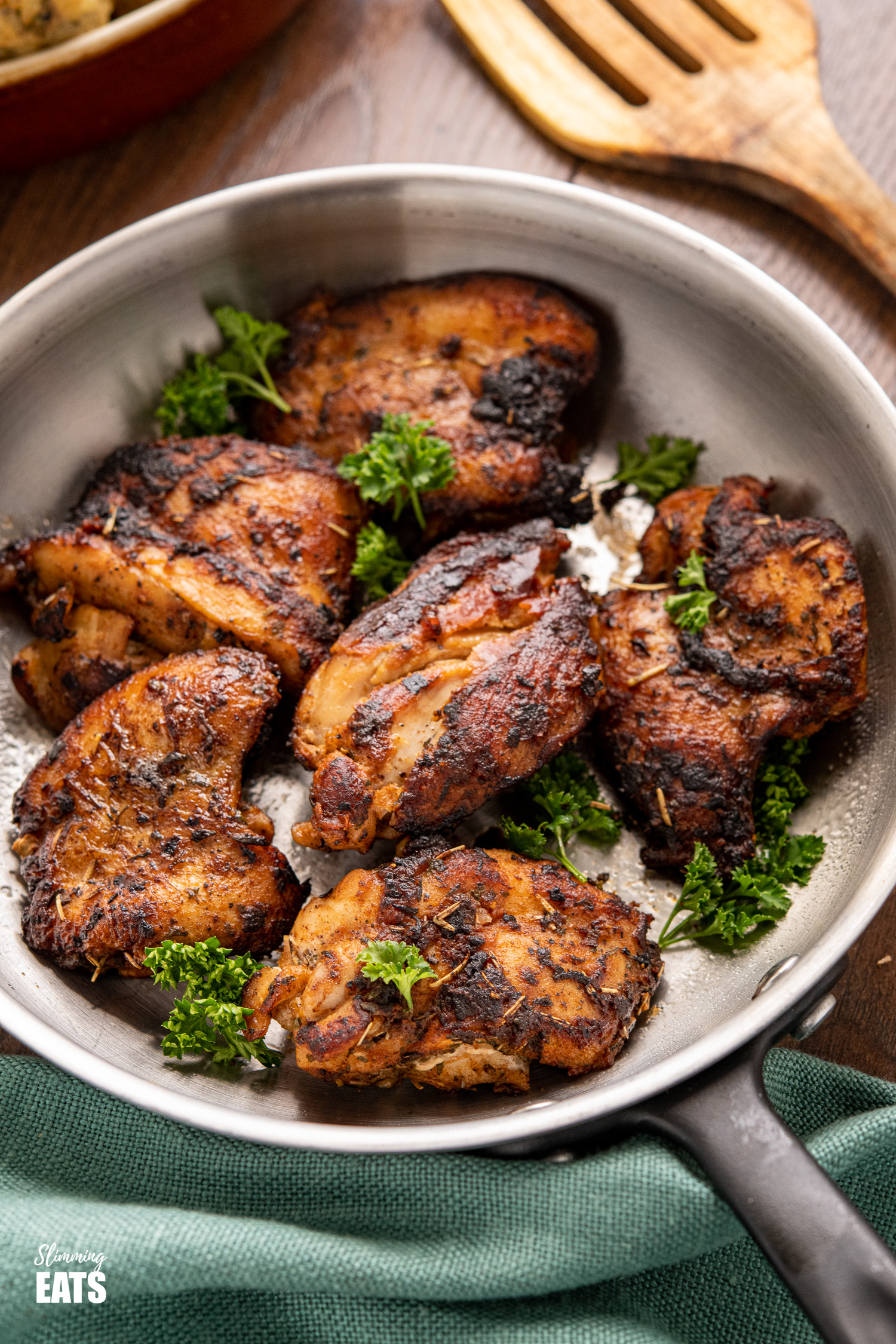 Seasoned Chicken in frying pan garnished with parsley, wooden spatula to the top right