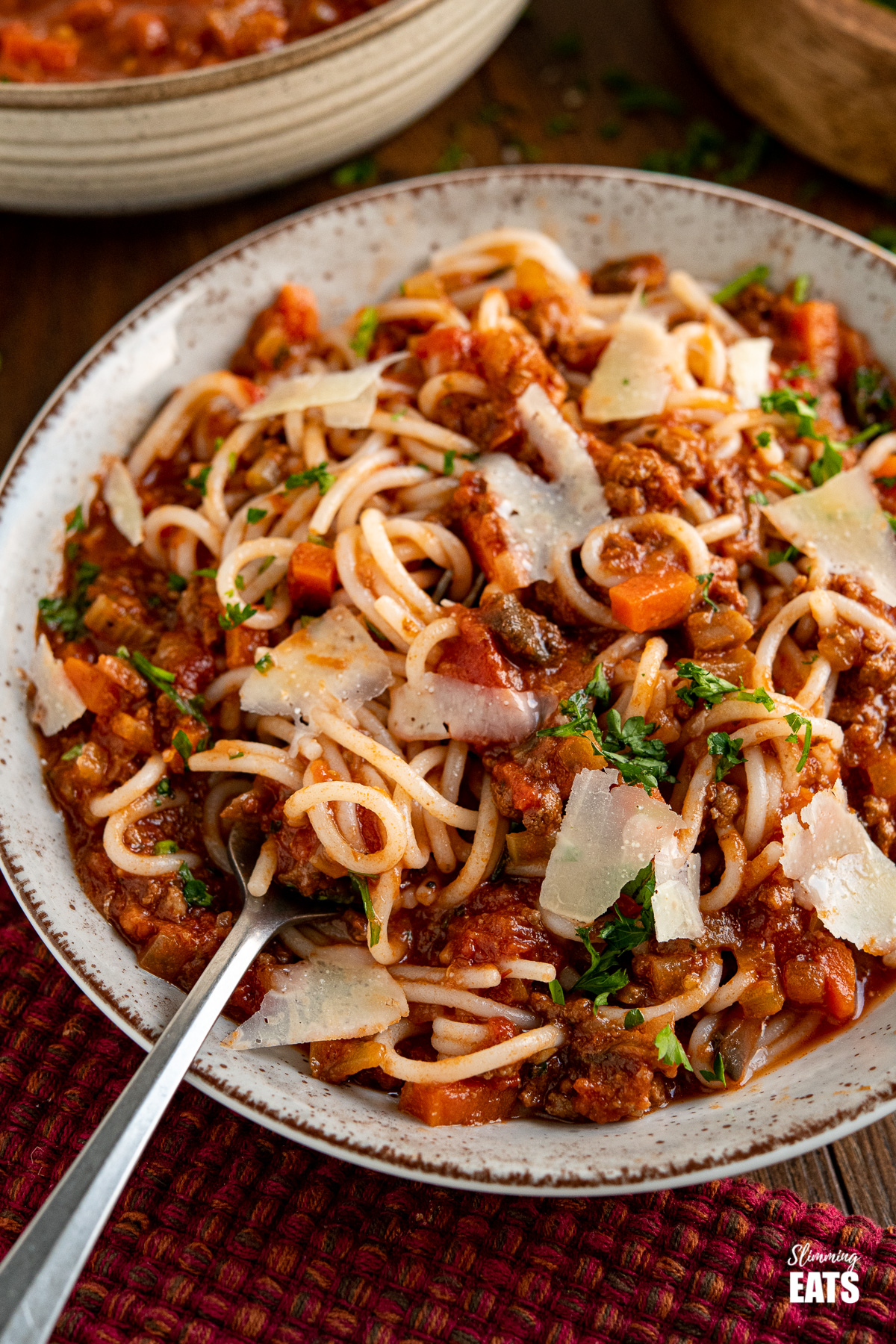 Slow Cooker Bolognese Sauce mixed with rice spaghetti and topped with shavings of parmesan in grey brown speckled bowl