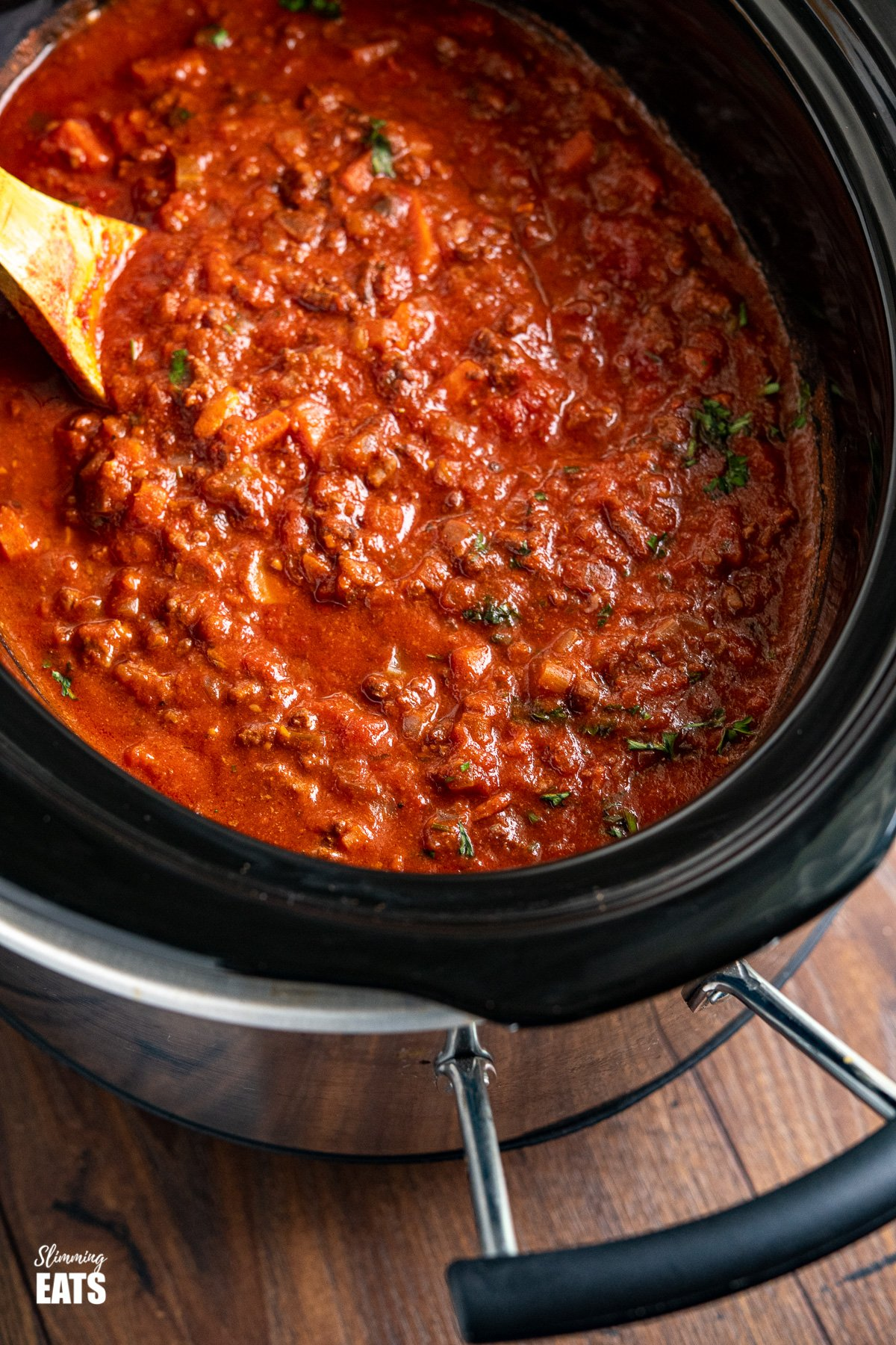 close up of Slow Cooker Bolognese Sauce in slow cooker with wooden spoon