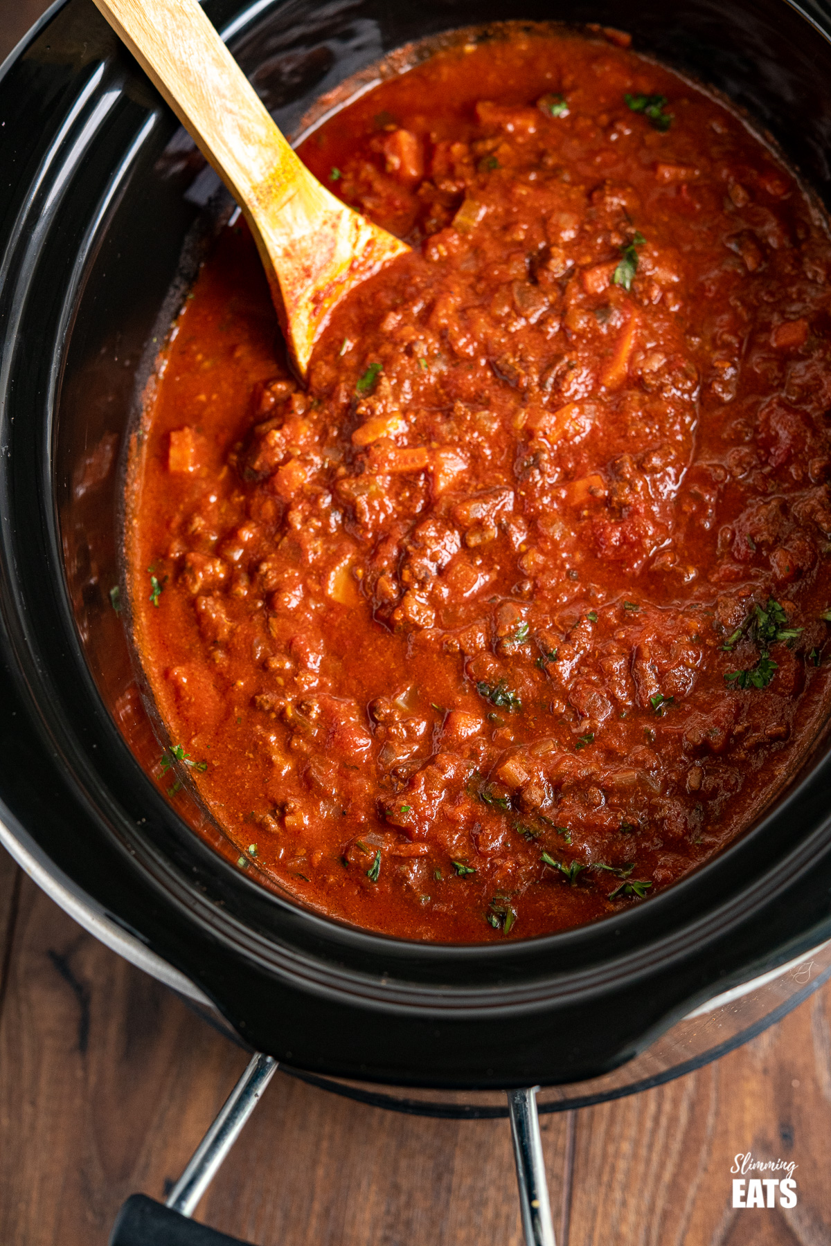 Slow Cooker Bolognese Sauce in slow cooker with wooden spoon