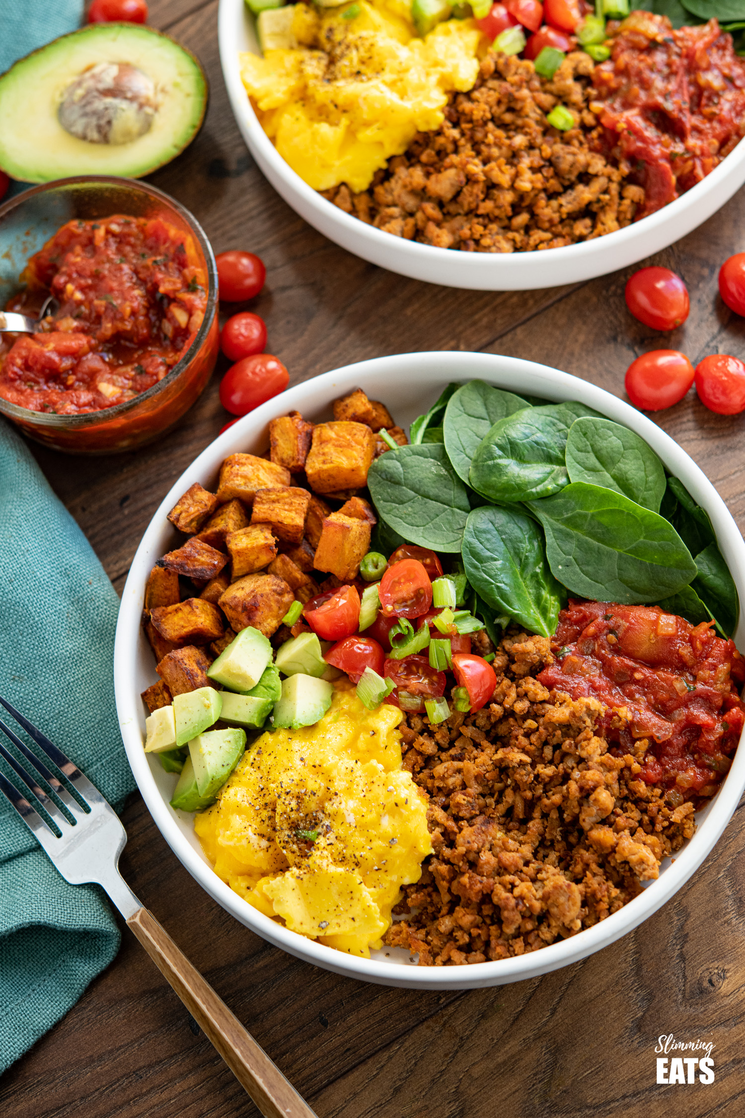 turkey taco meat, eggs, spinach, sweet potato, avocado, tomatoes in a bowl with additional bowl in background with scattered tomatoes and half an avocado
