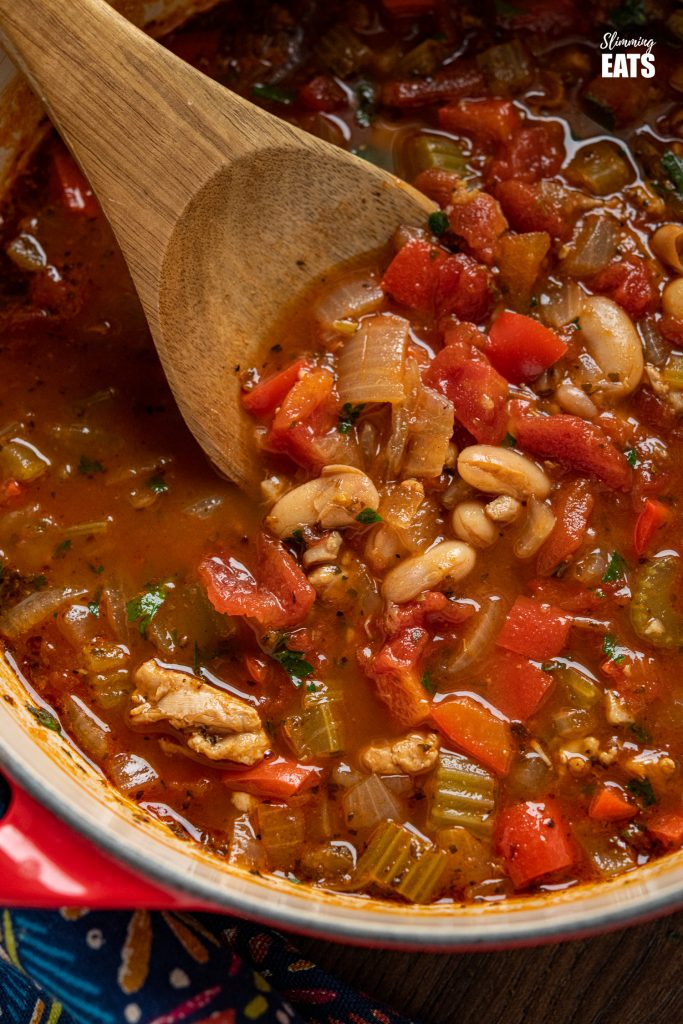 chicken, tomato and white bean soup in cerise cast iron pot